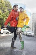 Happy couple in wellingtons splashing in rainy street Stock Photos