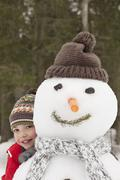 Portrait of smiling boy behind snowman with stocking-cap Stock Photos