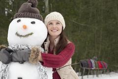 Happy woman hugging snowman in woods Stock Photos