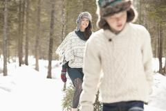 Mother and son dragging fresh Christmas tree in snowy woods Stock Photos
