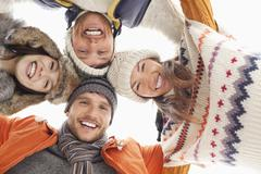 Low angle portrait of happy friends in huddle - stock photo
