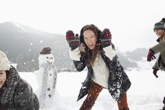 Enthusiastic friends enjoying snowball fight in field Stock Photos