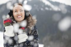 Happy woman wearing ear muffs and gloves in snow - stock photo