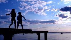 Two kids throwing the stones to sea Stock Footage