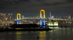 Stock Video Footage of Time lapse of the Rainbow Bridge at night as seen from Odaiba with pan right
