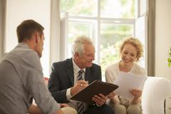 Financial advisor talking to couple in living room - stock photo