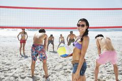Portrait of smiling woman playing beach volleyball with friends Stock Photos