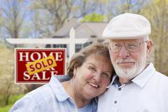 Senior Couple in Front of Sold Real Estate Sign and House - stock photo