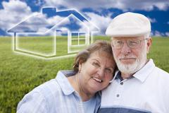 Loving Senior Couple Standing in Grass Field with Ghosted House on the Horizo - stock photo