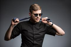 Stylish man in black shirt and mirrored sunglasses - stock photo