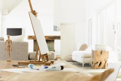 Easel and paint tubes on table Stock Photos