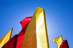 Red and yellow flags fluttering in the wind against blue sky Stock Photos