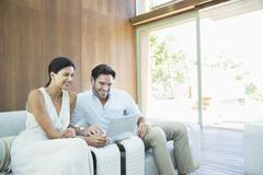 Couple using laptop on armchairs - stock photo