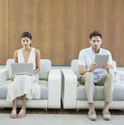 Couple using digital tablet and laptop in armchairs Stock Photos