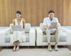 Couple using laptop and digital tablet in armchairs Stock Photos