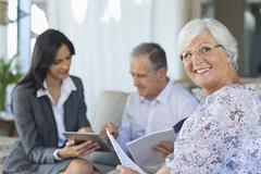 Financial advisor talking to couple on sofa Stock Photos