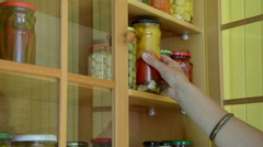 Girl hand put canned glass pot of peppers to food storage shelf Stock Footage