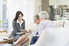 Financial advisor using tablet computer with clients Stock Photos
