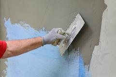 Wall insulation, spreading mortar over mesh - stock photo