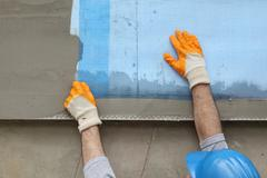 Styrofoam facade insulation, installing mesh - stock photo