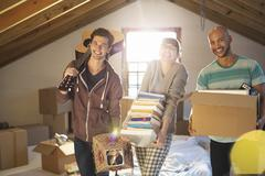 Friends unpacking boxes in attic - stock photo
