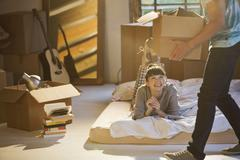 Couple unpacking boxes in attic Stock Photos