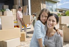 Mother and daughter smiling by moving van in driveway - stock photo