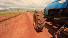 Farm Tractor going down Dirt Road in rural Africa Stock Footage