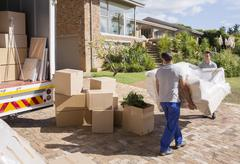 Movers carrying sofa from moving van to house - stock photo