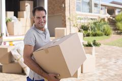 Portrait of man carrying cardboard box from moving van - stock photo