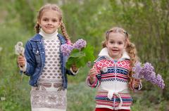 Two girls with dandelions and lilacs Stock Photos