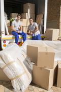 Movers sitting in moving van in driveway - stock photo