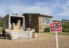 Sold sign and moving van outside house - stock photo