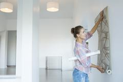 Woman hanging wallpaper in new house - stock photo