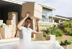 Man holding cardboard box overhead near moving van in driveway - stock photo