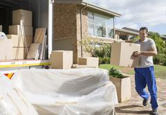 Man carrying cardboard box to moving van in driveway Stock Photos