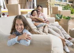 Portrait of smiling family on sofa in driveway near moving van - stock photo