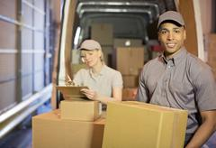 Stock Photo of Delivery people loading boxes into van