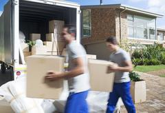 Movers carrying cardboard boxes in driveway past moving van - stock photo