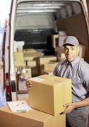 Delivery boy loading boxes into van - stock photo