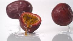 Passion fruit falling and bouncing on water surface. Slow Motion. Stock Footage