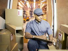 Delivery boy checking boxes in van - stock photo