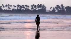 Woman walking on the beach at sunset, Sri Lanka Stock Footage