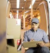 Stock Photo of Delivery boy using clipboard in van