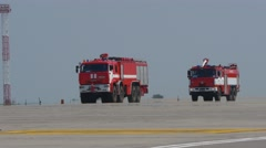 Fire trucks arriving at airport taxiway Stock Footage