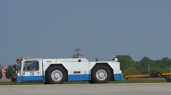 Pushback tug carrying a towbar on apron arriving at taxiway Stock Footage