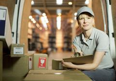 Delivery girl checking boxes in van Stock Photos