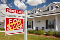 Sold Short Sale Real Estate Sign and House - Left - stock photo