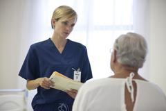 Nurse and older patient talking in hospital room Stock Photos