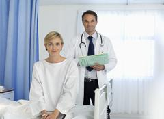 Doctor and patient smiling in hospital room Stock Photos